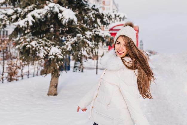 Wintersneeuwgeluk van vreugdevolle aantrekkelijk meisje met lang donkerbruin haar lopen op straat.