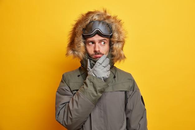 Wintersport en recreatie concept. ernstige bedachtzame man in bovenkleding gekleed in jas en handschoenen draagt een snowboardbril en denkt na over plannen voor vrije tijd.