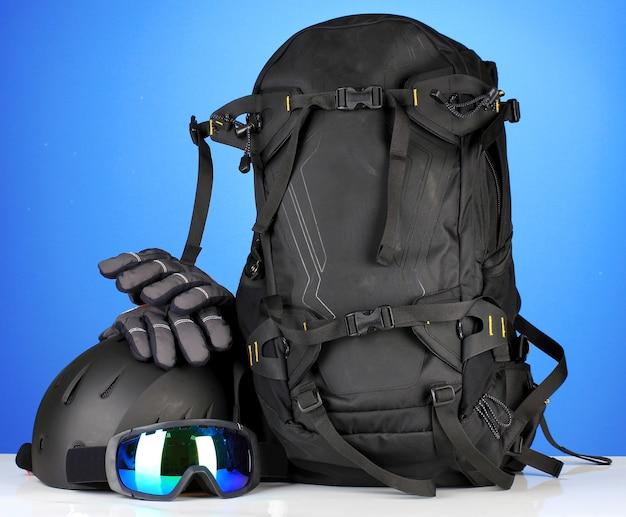 Wintersportbril, helm en handschoenen, rugzak, op blauw