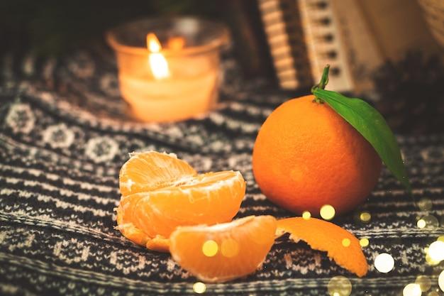 Winterstilleven met mandarijnen, mandarijnplakken op gebreide truiachtergrond met garlad gezellige bokeh, kopieer ruimte. hoge kwaliteit foto