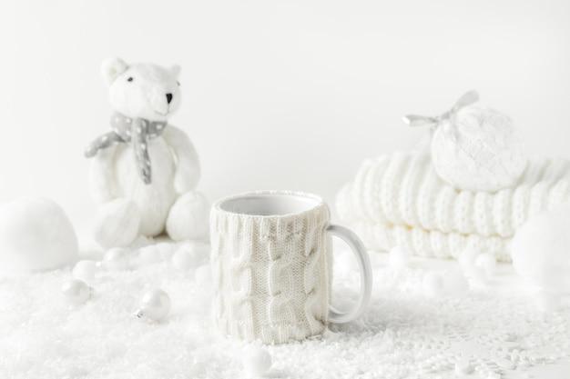 Winterstilleven met mok thee, gebreide teddybeer, wit decor.