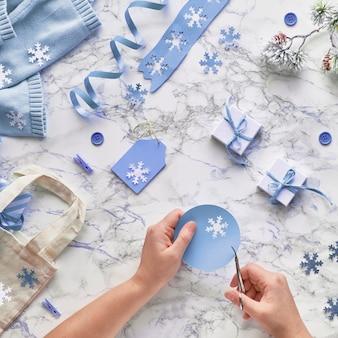 Wintertijd, creatief plat leggen met verschillende winterdecoraties, kerstboomtakjes en handen die tags snijden