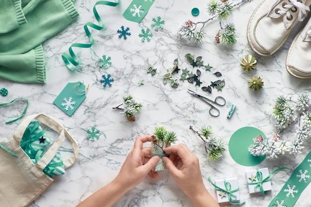 Wintertijd, creatieve plat met verschillende winter ambachtelijke supploes, kerstboom twijgen en handen versieren geschenkdoos