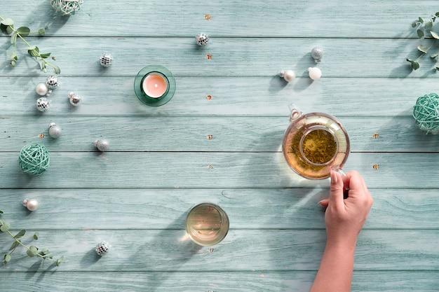 Wintertijd thee, regeling met glazen theepot, glas thee in de hand op lichtblauwe munt houten achtergrond. kerst versiering..