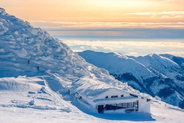 Wintertoppen van bergen in de zonnige ochtend. lichte mist in de valleien. snow cafe en twee onherkenbare toeristen