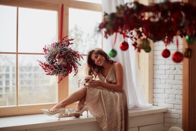 Wintervakantie decor. warme kleuren. charmante en gelukkige vrouw in beige jurk