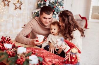 Wintervakantie decoraties. Warme kleuren. Familie portret. Moeder, vader en hun dochtertje