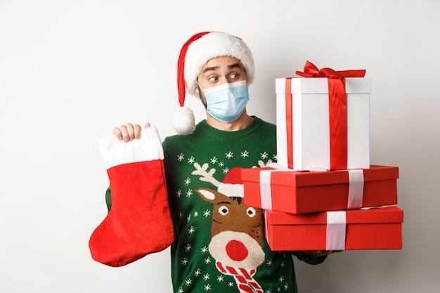 Wintervakantie en covid-19 concept. gelukkige man met gezichtsmasker en kerstmuts die geschenken brengt, kerstsok vasthoudt en dozen presenteert, staande op een witte achtergrond