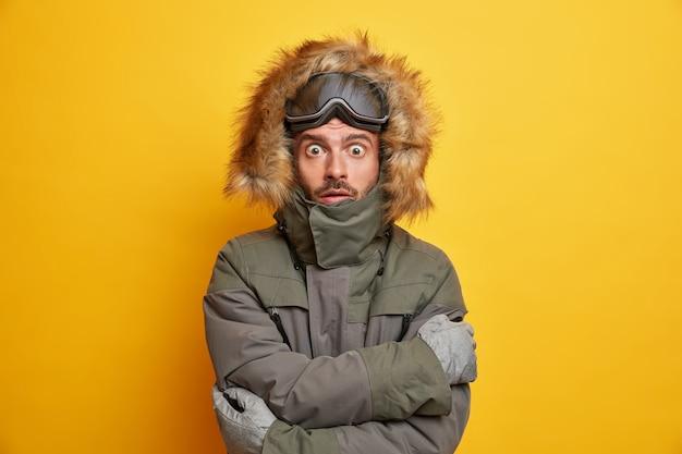 Wintervakantie en extreme sport concept. geschokte snowboarder beeft van de kou omhelst zichzelf terwijl hij probeert op te warmen tijdens een ijzige dag in een bergskigebied.
