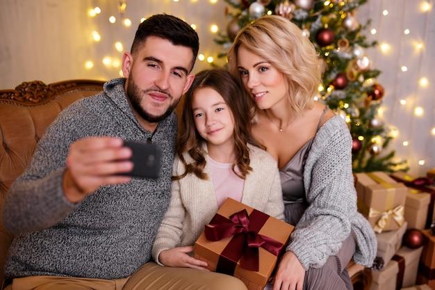 Wintervakantie en familieconcept - gelukkig jong gezin dat selfie-foto maakt met smartphone in woonkamer met versierde kerstboom
