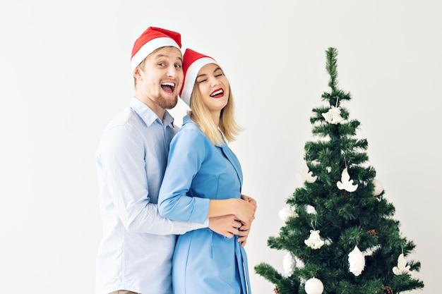 Wintervakantie en familieconcept - gelukkig jong stel in de buurt van de kerstboom thuis.