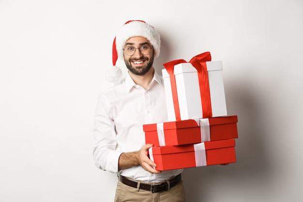Wintervakantie en feest. gelukkige kerel brengt kerstcadeautjes, cadeautjes vasthouden en het dragen van kerstmuts, staande op een witte achtergrond.