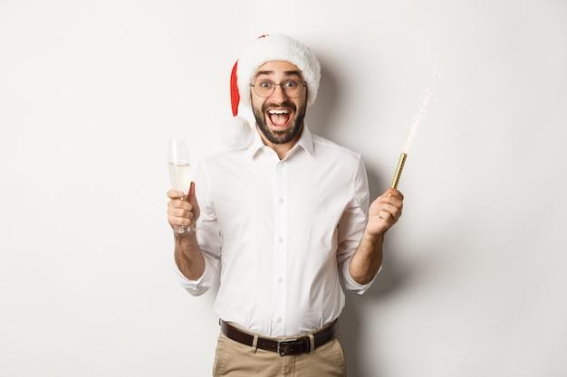 Wintervakantie en feest. gelukkige kerel in kerstmanhoed die zich op nieuwjaarsfeest verheugen, champagne drinken en schreeuwen van vreugde, witte achtergrond.