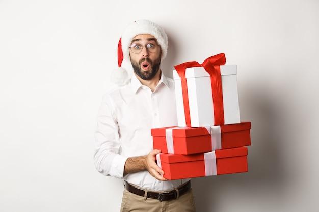 Wintervakantie en feest. opgewonden man met kerstcadeaus en op zoek verbaasd, met kerstmuts, staande op een witte achtergrond.