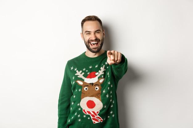 Wintervakantie en kerst. gelukkige jonge man die oudejaarsavond viert, met de vinger naar je wijst en lacht, staande op een witte achtergrond