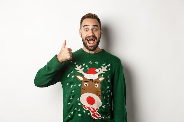 Wintervakantie en kerst. opgewonden blanke man die duim omhoog laat zien en verbaasd kijkt, staande in een groene trui tegen een witte achtergrond
