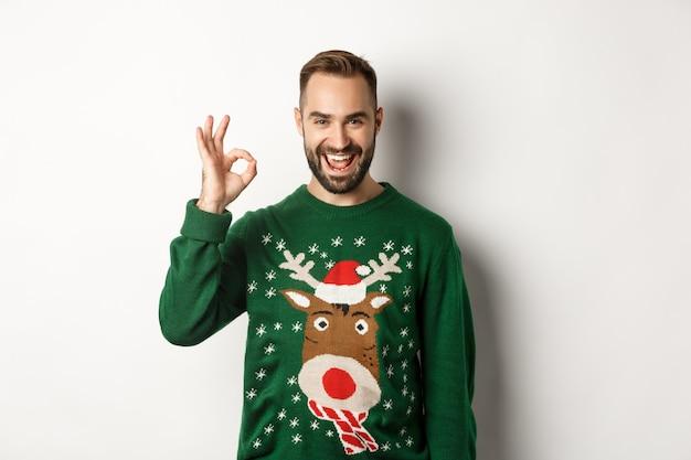 Wintervakantie en kerst. tevreden bebaarde man in groene trui, met ok-teken in goedkeuring, als iets goeds, staande op een witte achtergrond.