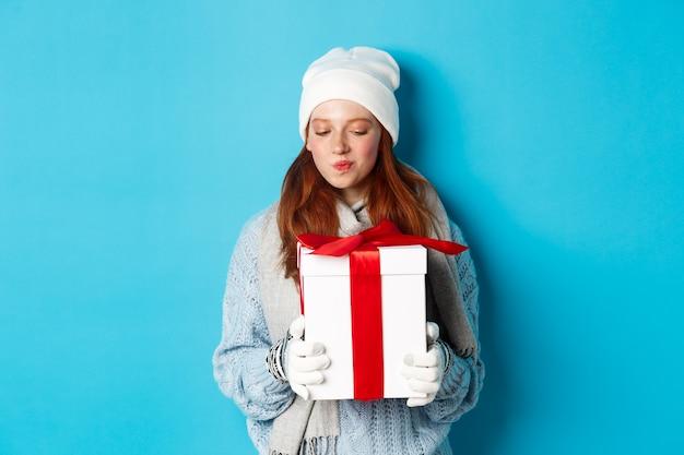 Wintervakantie en kerst verkoopconcept. geïntrigeerd roodharig meisje dat cadeau vasthoudt, nieuwsgierig naar doos met cadeau staart, probeert te raden wat erin zit, staande over blauwe achtergrond