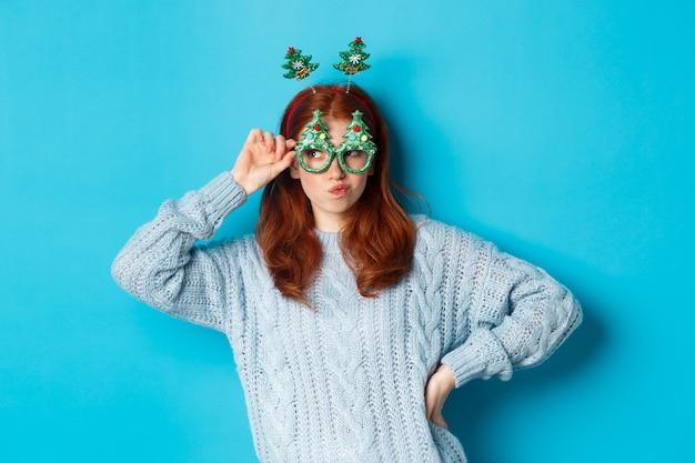 Wintervakantie en kerst verkoopconcept. mooi roodharig vrouwelijk model dat nieuwjaar viert, met een grappige feesthoofdband en een bril, die lacht op een domme, blauwe achtergrond.