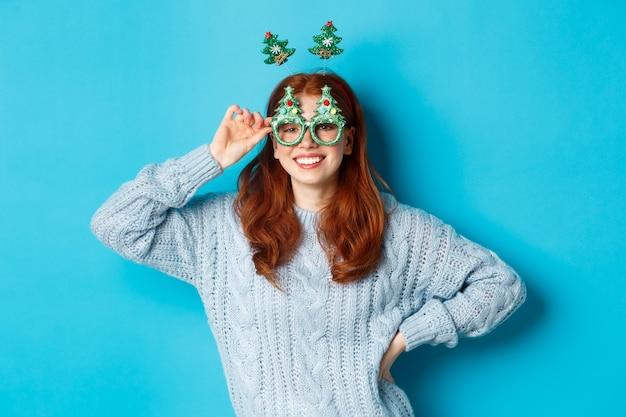 Wintervakantie en kerst verkoopconcept. mooi roodharig vrouwelijk model dat nieuwjaar viert, met een grappige feesthoofdband en een bril, glimlachend in de camera.