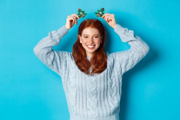 Wintervakantie en kerst verkoopconcept. mooi roodharig vrouwelijk model dat nieuwjaar viert, met grappige feesthoofdband en trui, glimlachend in de camera