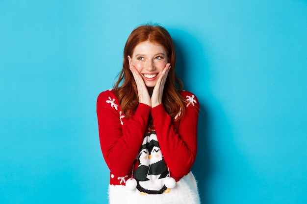 Wintervakantie en kerstavond concept. aanbiddelijk roodharige meisje bloost en raakt wangen van geluk, glimlachend en kijkt naar promo in de linkerbovenhoek, blauwe achtergrond.