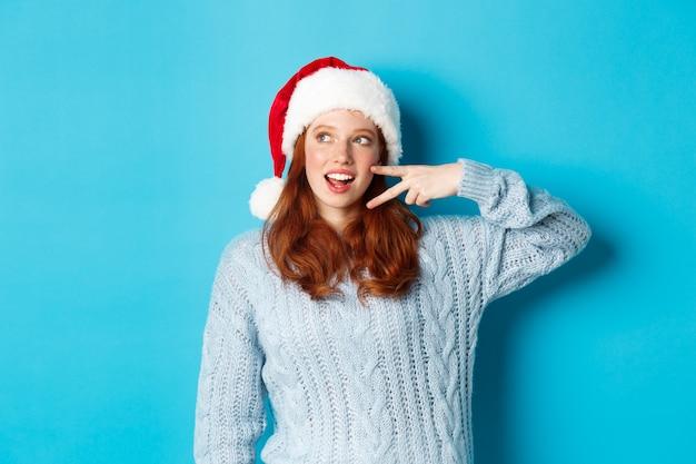 Wintervakantie en kerstavond concept. gelukkig tienermeisje met rood haar, dat santahoed draagt, genietend van nieuwjaar, vredesteken toont en staren links bij promo, die zich over blauwe achtergrond bevindt.
