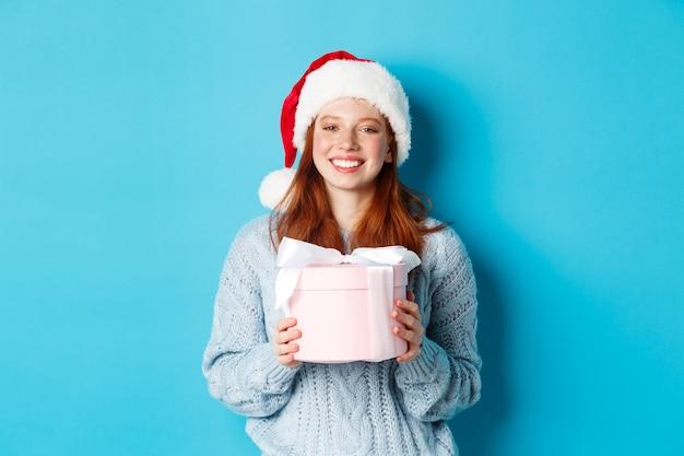 Wintervakantie en kerstavond concept. glimlachend roodharige meisje in trui en kerstmuts, nieuwjaar cadeau houden en kijken naar camera, staande tegen blauwe achtergrond.