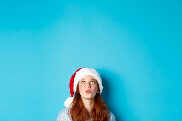 Wintervakantie en kerstavond concept. hoofd van een mooi roodharig meisje in een kerstmuts, verschijnt van onderen en kijkt omhoog naar het logo onder de indruk, ziet promo-aanbieding, blauwe achtergrond
