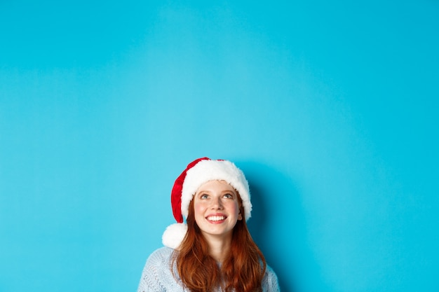 Wintervakantie en kerstavond concept. hoofd van schattig roodharig meisje in kerstmuts, verschijnt van onderen en kijkt omhoog naar kopieerruimte, starend naar logo, staande over blauwe achtergrond