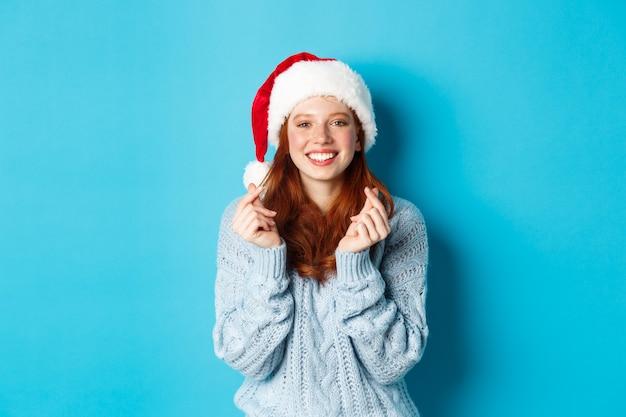 Wintervakantie en kerstavond concept. hoopvol roodharig meisje in kerstmuts, wensen doen op kerstmis met gekruiste vingers, kerstmuts dragen, staande over blauwe achtergrond