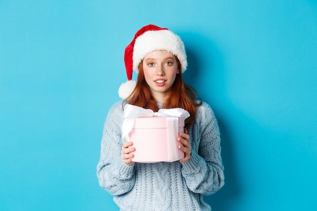 Wintervakantie en kerstavond concept. leuk roodharig meisje met kerstmuts, nieuwjaarscadeau vasthoudend en kijkend naar de camera, staande tegen een blauwe achtergrond.