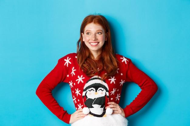 Wintervakantie en kerstavond concept. mooi roodharig tienermeisje in kersttrui, links kijkend naar logo, tevreden glimlachend, hand in hand op taille, blauwe achtergrond