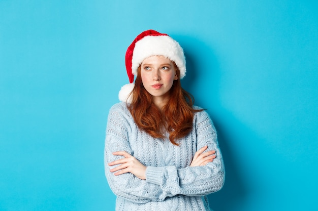 Wintervakantie en kerstavond concept. nadenkende roodharige vrouw in kerstmuts en trui, naar links kijkend en peinzend, kerst plannen maken, staande over blauwe achtergrond.