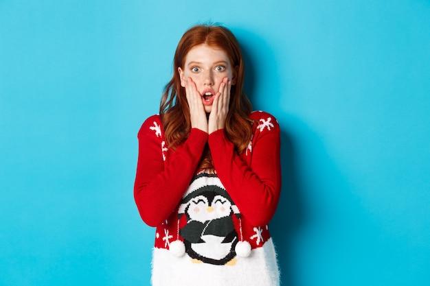 Wintervakantie en kerstavond concept. onder de indruk en sprakeloos roodharig meisje hijgend, starend naar de camera met ongeloof, staande in kersttrui tegen blauwe achtergrond