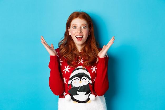 Wintervakantie en kerstavond concept. verrast roodharig meisje dat goed nieuws ontvangt, handen opsteekt en verbaasd naar adem snakkend, vol ontzag voor blauwe achtergrond