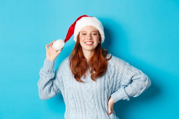 Wintervakantie en kerstavond concept. vrolijk roodharige tienermeisje met kerstmuts en tevreden glimlachend, staande in trui tegen blauwe achtergrond