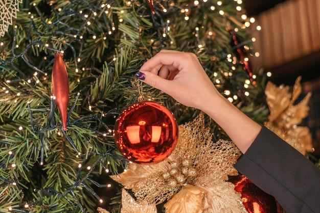 Wintervakantie en mensen concept close-up van jonge vrouw hand kerstboom versieren met rode bal over sneeuw