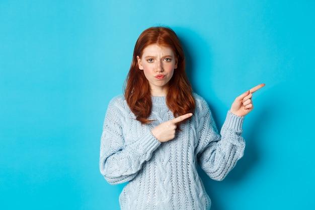 Wintervakantie en mensen concept. ingewikkeld roodharig meisje starend besluiteloos, wijzend met de vingers naar het logo en fronsend, verward tegen een blauwe achtergrond.