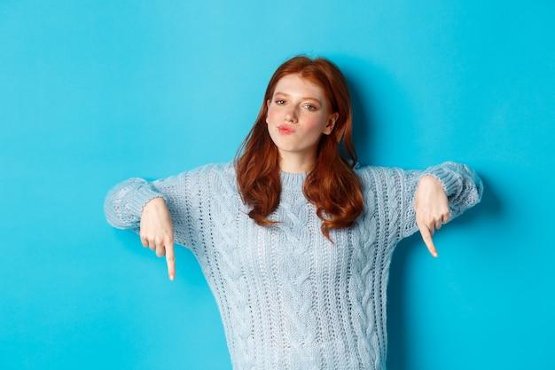 Wintervakantie en mensen concept. nadenkend roodharig tienermeisje in trui, met de vingers naar beneden wijzend en nadenkend, een beslissing nemend, staande over een blauwe achtergrond.