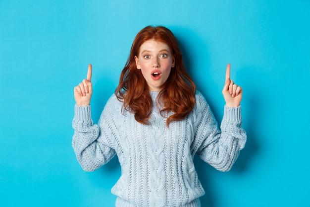 Wintervakantie en mensen concept. verbaasd roodharige tienermeisje dat met de vingers omhoog wijst, reclame toont en onder de indruk van de camera staart, blauwe achtergrond.