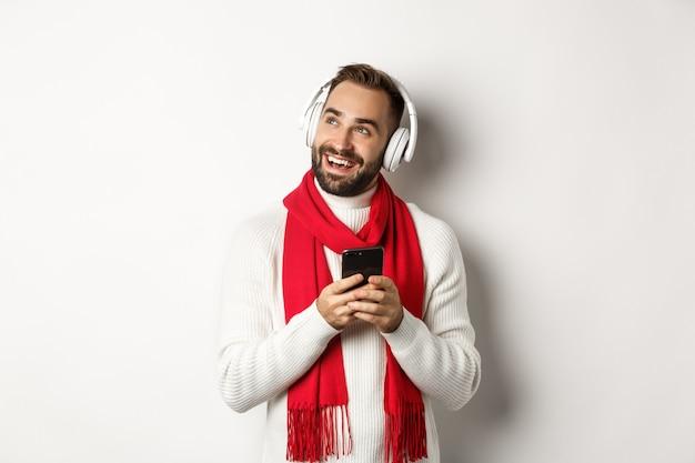 Wintervakantie en technologie concept. gelukkig man luisteren naar muziek podcast op koptelefoon, mobiele telefoon vasthouden en kijken naar lege ruimte, witte achtergrond