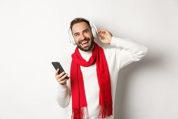 Wintervakantie en technologie concept. man die geniet van het luisteren van muziek in een koptelefoon, tevreden kijkt, smartphone vasthoudt, trui met sjaal draagt, witte achtergrond