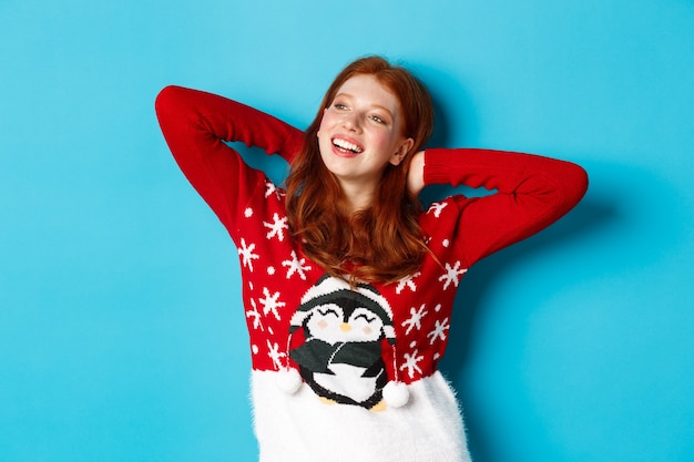 Wintervakantie en viering concept. ontspannen tienermeisje hand in hand achter het hoofd en kijken naar links naar promo, rustend op kerstavond, staande over blauwe achtergrond.