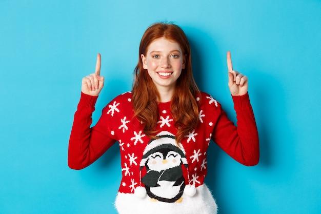 Wintervakantie en viering concept. schattige roodharige meisje in kerst trui, glimlachend en wijzende vingers op promo logo, staande op blauwe achtergrond.