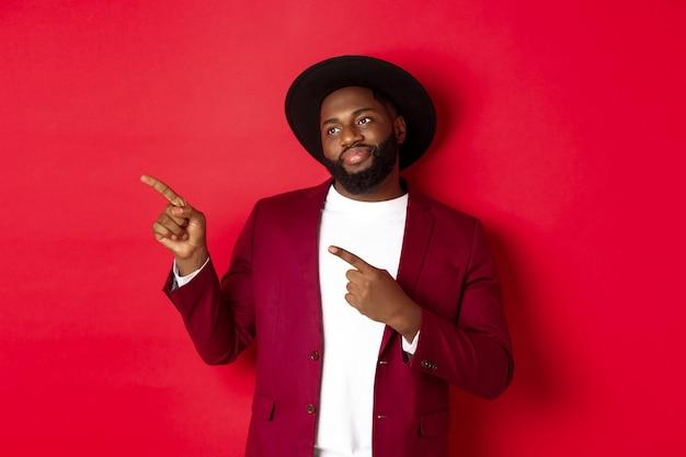 Wintervakantie en winkelconcept. geërgerde afro-amerikaanse man grijnzend gehinderd, wijzend en kijkend naar het logo in de linkerbovenhoek, rode achtergrond