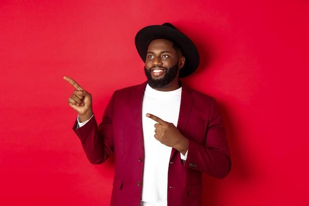 Wintervakantie en winkelconcept. gelukkige zwarte man die naar links wijst en glimlacht, met een nieuwjaarspromo-aanbieding op rode achtergrond.
