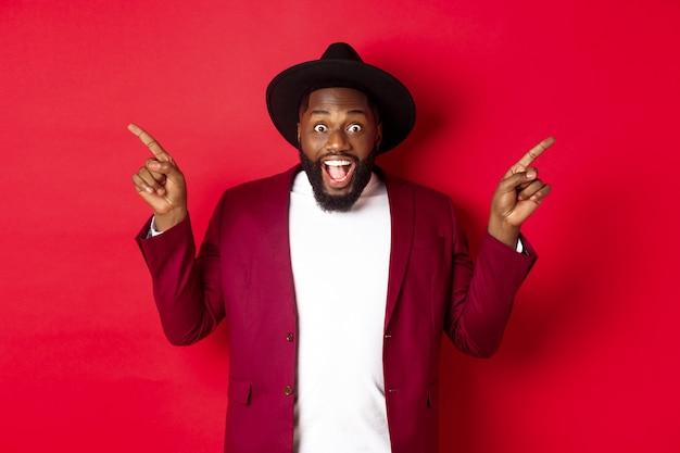 Wintervakantie en winkelconcept. vrolijke zwarte man die lacht en twee promo's laat zien, wijzende vingers zijwaarts naar kopieerruimten, rode achtergrond