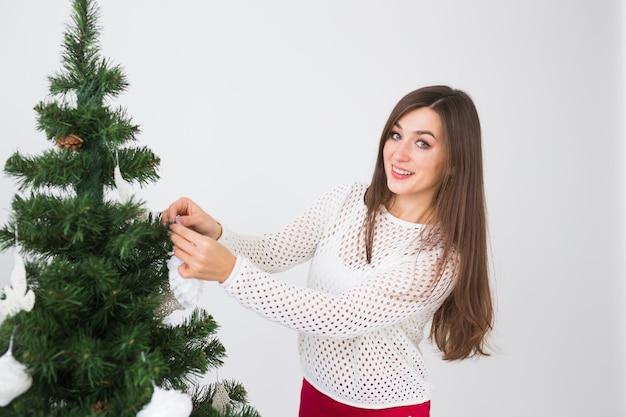 Wintervakantie, kerstmis en mensenconcept - mooie jonge vrouw die een kerstboom in witte kamer versiert