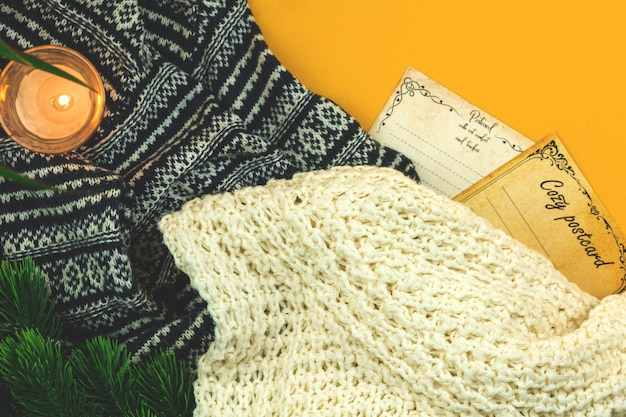 Wintervakantie wenskaart, ansichtkaarten, gezellige postersjabloon, wollen en gebreide trui, kaars, kopieer ruimtefoto